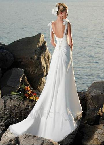 bride standing on rocks by the sea